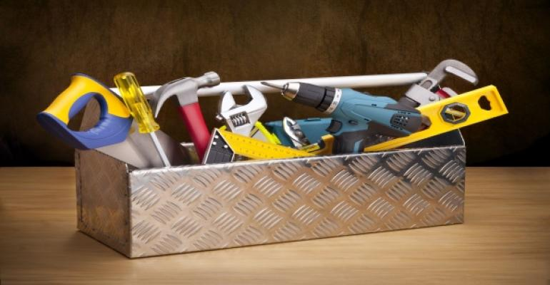Silver toolbox with assorted disorganized tools coming out of the top
