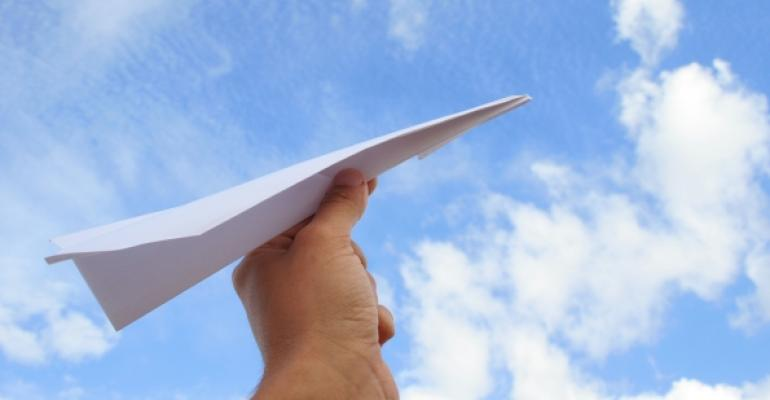 hand with paper airplane blue sky background