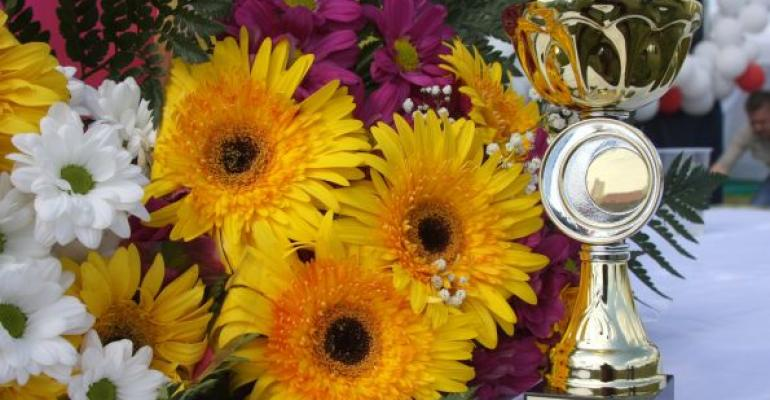 gold and silver trophy on white table with bouquet of flowers in background