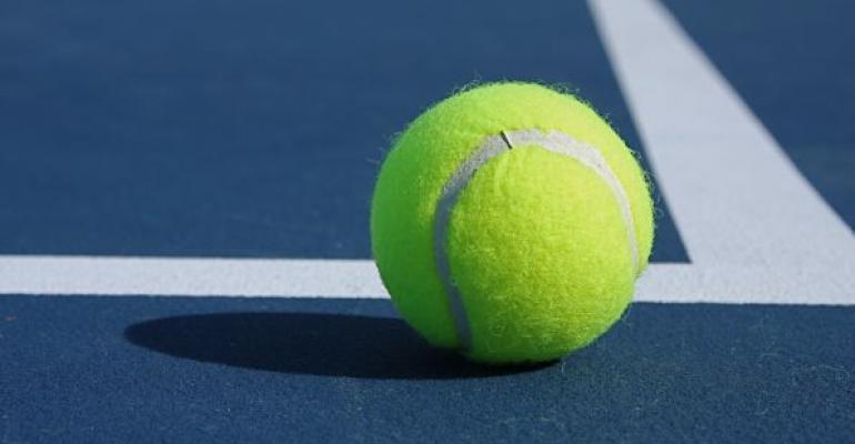 Yellow tennis ball on white tennis court baseline