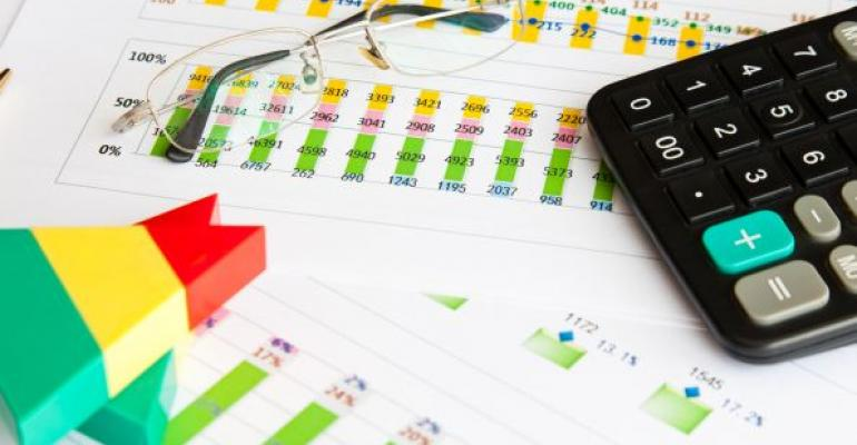 financial documents with eraser glasses calculator resting on top