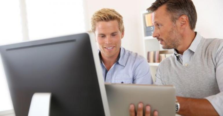 two men working with tablet in front of computer