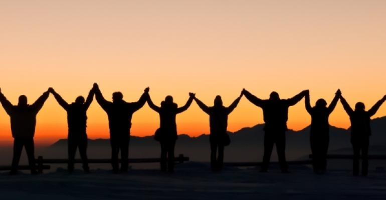 silhouettes of 8 people with arms raised at sunset