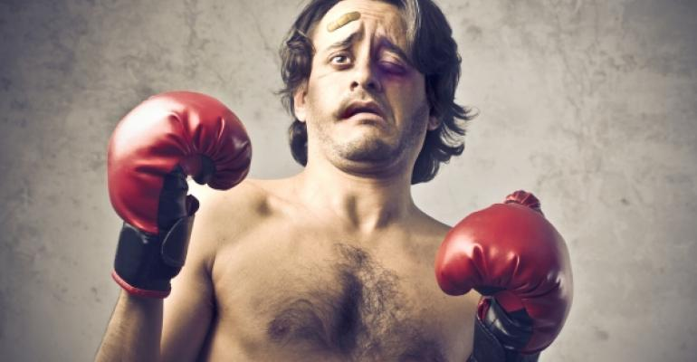 shirtless man with bruised face and boxing gloves
