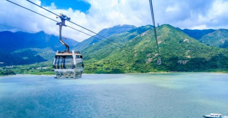 Cable car on line en route to green island blue sky background