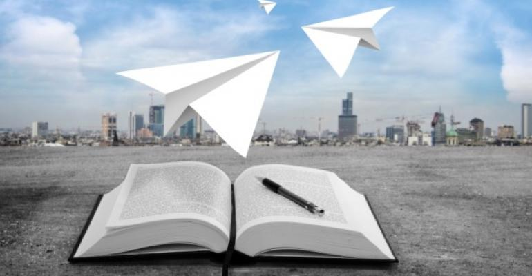 open book and paper airplanes in foreground city skyline in background