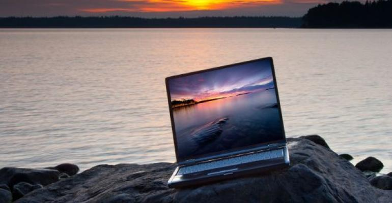 Laptop on rock in front of water displaying picture of sunset