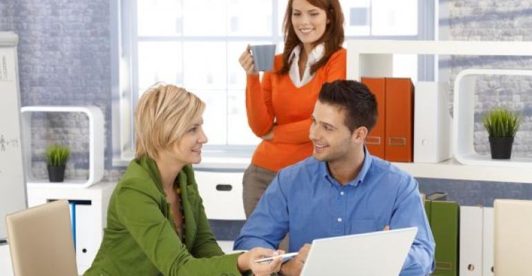 Three people in an office sitting around a laptop