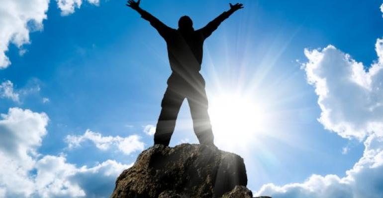 person on top of mountain with arm outstretched and sun silhouetting