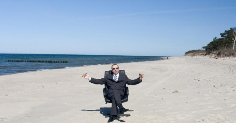 guy in business suit sitting in desk chair on a beach