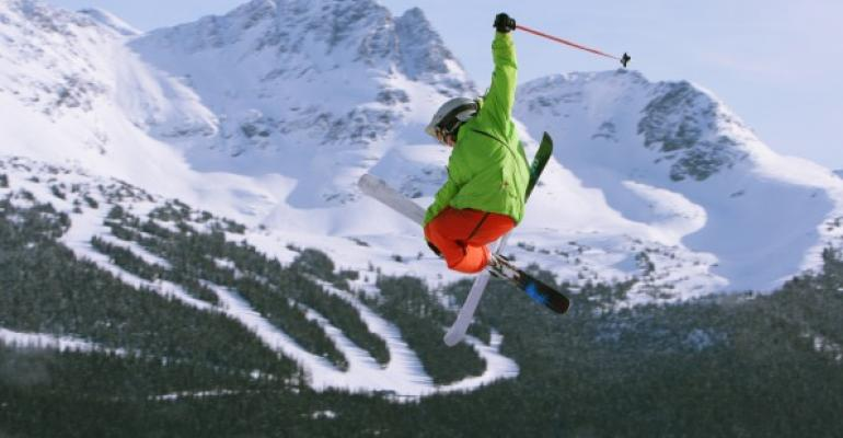 skiier jumping in green jacket Mountainous background