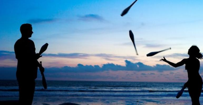 Man and woman juggling at sunset by the ocean