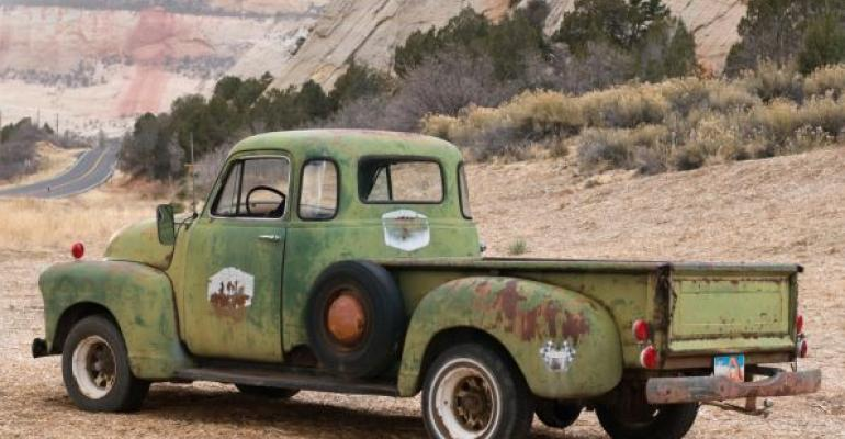 old green pickup by the side of the road