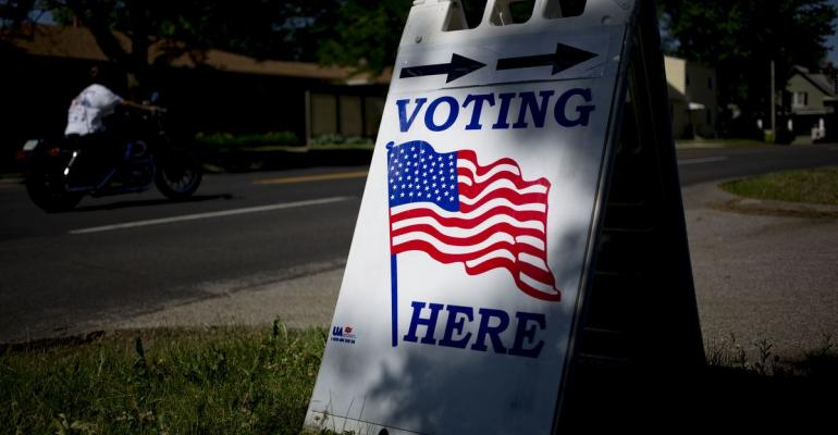 """A """"Voting Here"""" sign is displayed outside at a polling location in Davenport, Iowa, U.S., on Tuesday, June 5, 2018. Photographer: Daniel Acker/Bloomberg"""