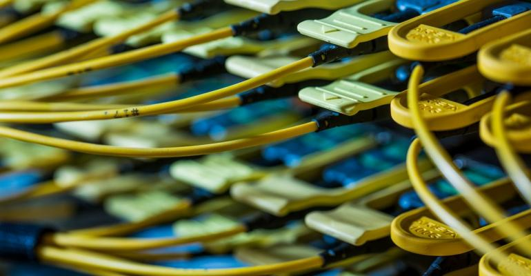 Fiber optic cables feed into a switch inside a communications room at an office in the U.K. Photographer: Jason Alden/Bloomberg