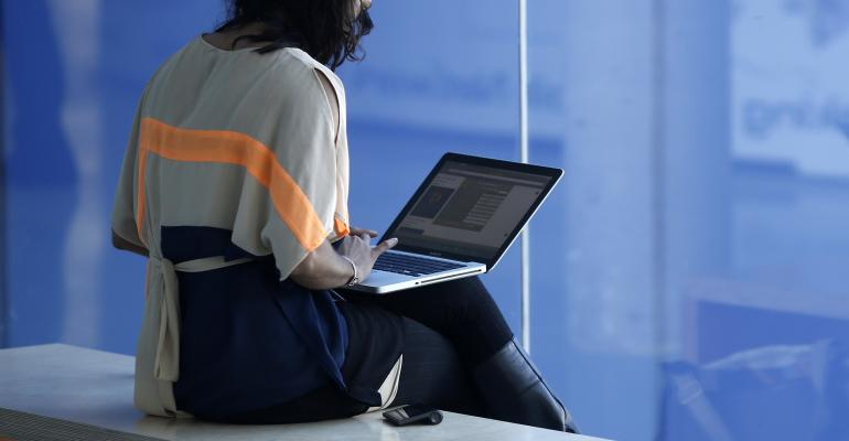 An attendee sits and works on a laptop computer on the opening day of the Mobile World Congress in Barcelona Photographer: Simon Dawson/Bloomberg