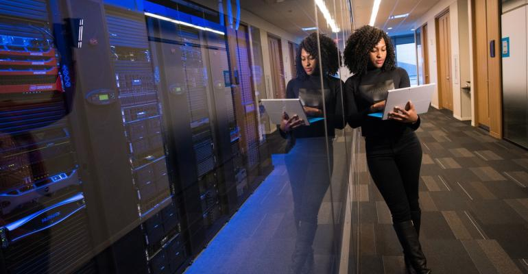 Women with laptop in data center.