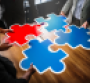 Businesspeople holding puzzle pieces.png
