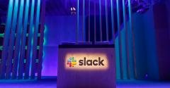 A Slack logo is illuminated on a conference stage at Slack Frontiers 2019