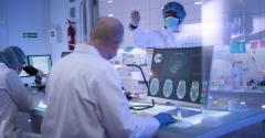 Multi ethnic doctors research team studying brainwave scanning wearing masks.jpg