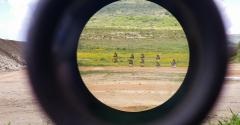 A look through an optical sight aimed at a group of potential targets at the range