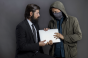 Photo-of-man-in-suit-and-man-in-hoodie-sweatshirt-and-mask,-both-holding-a-laptop