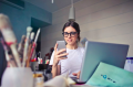 Woman holding smartphone at computer.png
