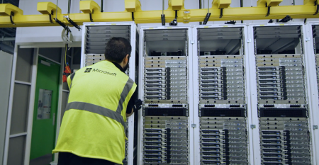 A Microsoft data center worker securing a rack of servers in place.