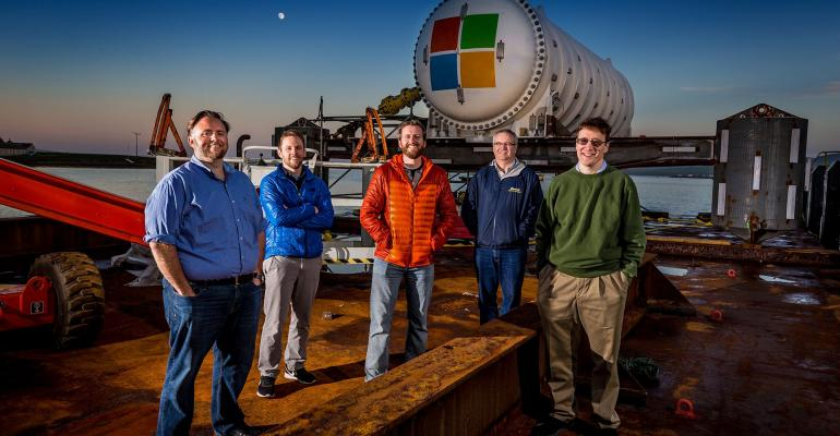 Microsoft's Project Natick team gathers on a barge tied up to a dock in Scotland's Orkney Islands in preparation to deploy the Northern Isles data center on the seafloor. Pictured from left to right are Mike Shepperd, senior R&D engineer, Sam Ogden, senior software engineer, Spencer Fowers, senior member of technical staff, Eric Peterson, researcher, and Ben Cutler, project manager.