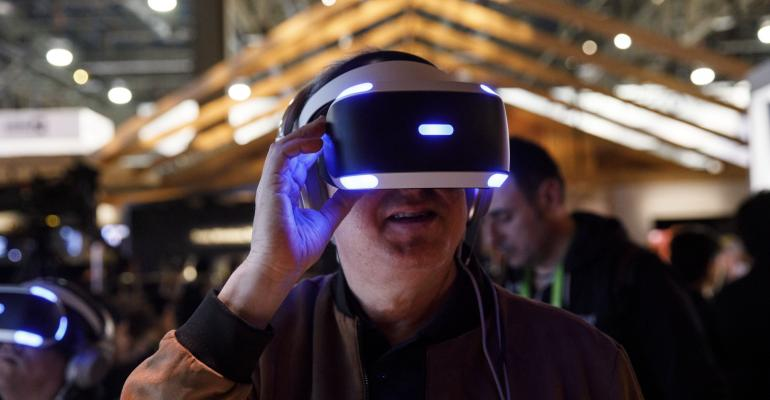 An attendee wears a Sony Corp. PlayStation 4 virtual reality (VR) headset at the company's booth during the 2018 Consumer Electronics Show (CES) in Las Vegas, Nevada, U.S., on Monday, Jan. 8, 2018. Electric and driverless cars will remain a big part of this year's CES, as makers of high-tech cameras, batteries, and AI software vie to climb into automakers' dashboards.