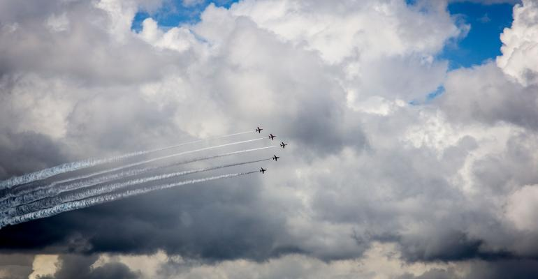 Fighter planes are backlit against the clouds