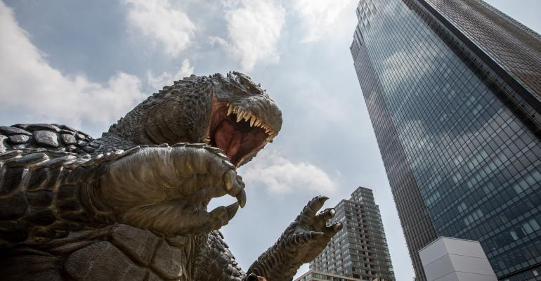 Godzilla faces off against a building.