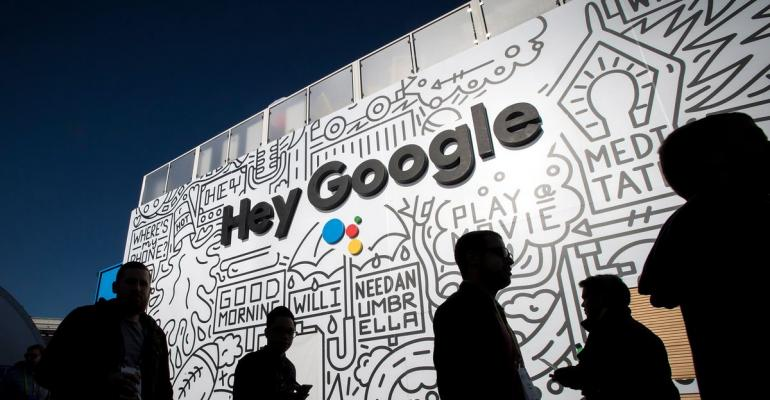 The silhouettes of attendees are seen at the Google Inc. booth during the 2018 Consumer Electronics Show (CES) in Las Vegas, Nevada, U.S., on Thursday, Jan. 11, 2018. Electric and driverless cars will remain a big part of this year's CES, as makers of high-tech cameras, batteries, and AI software vie to climb into automakers' dashboards. Photographer: David Paul Morris/Bloomberg