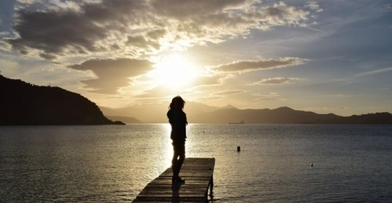 Person standing at end of dock close to sunset