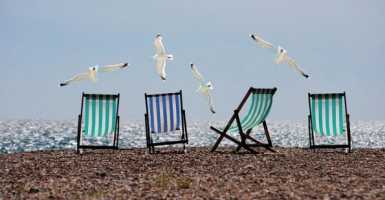 Beach chairs on the sand with sea gulls