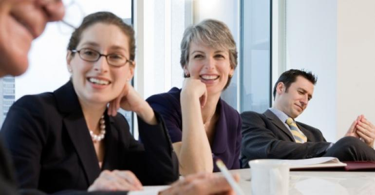 business people smiling around a conference table