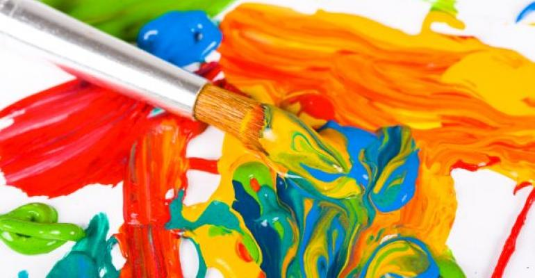 paint brush and bright colored paint on canvas