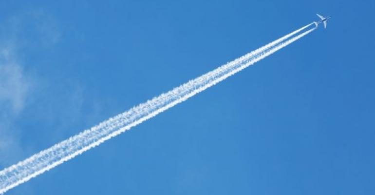 Plane flying across blue sky with cloud trail