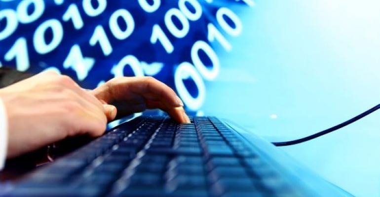 man typing on computer keyboard with data in the background