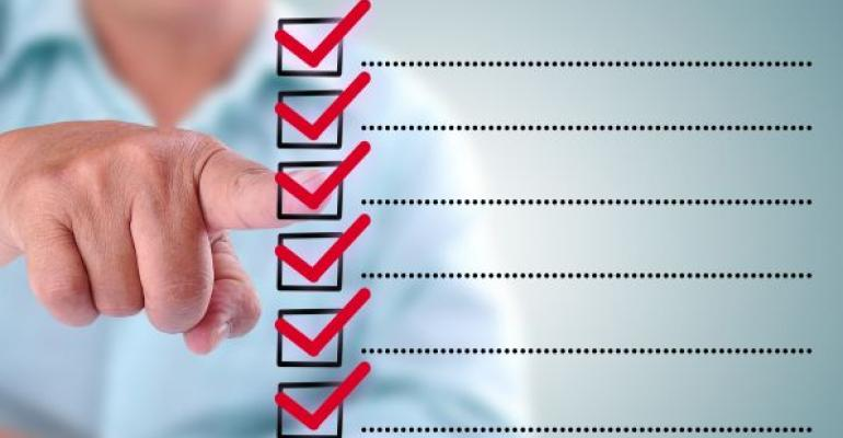 checklist with red check marks and male hand pointing at one check