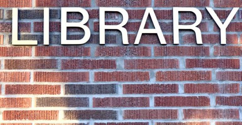 metal letters reading LIBRARY on red brick background