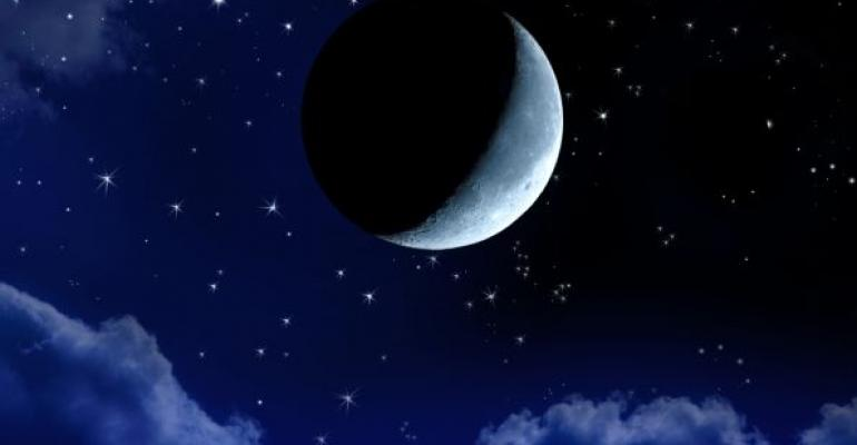 crescent moon in night sky with clouds and stars