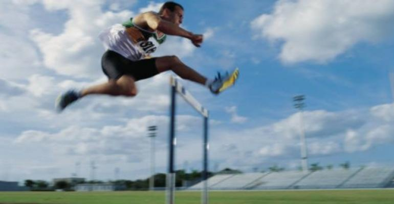 Man on track in running gear jumping over hurdle