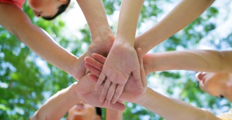 hands in a huddle green trees in background