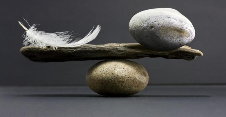 a stone and feather sitting on a piece of wood balanced on top of another rock