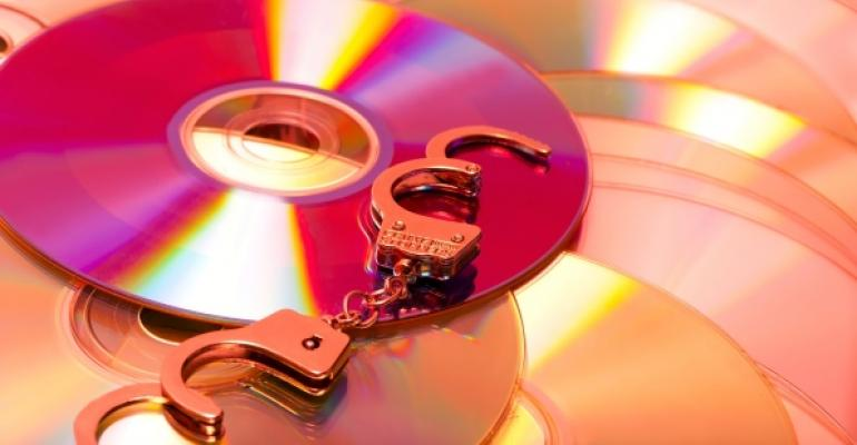 computer software disks with handcuffs laying on top