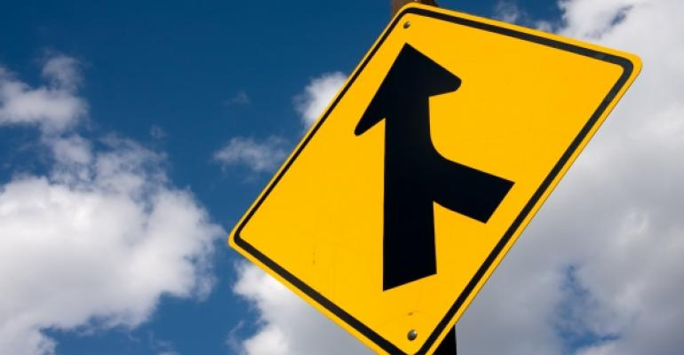 yellow road sign with merging arrow symbol blue cloudy sky background