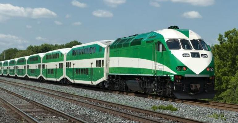 Green and white express train with clouds in background