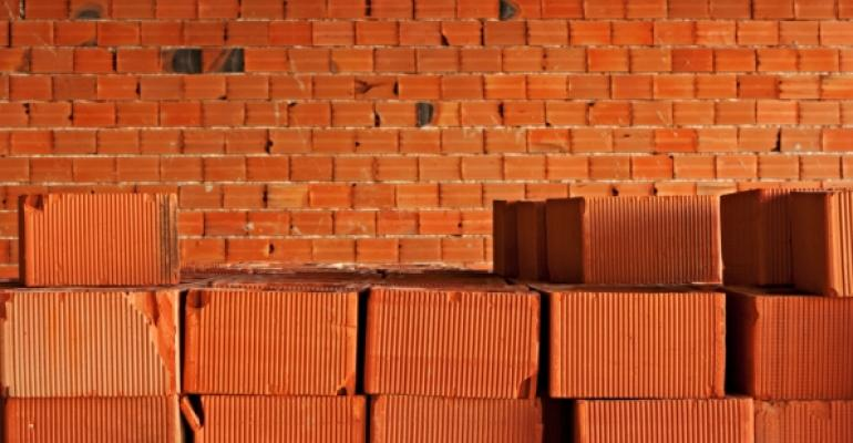 red bricks stacked in front of incomplete brick wall