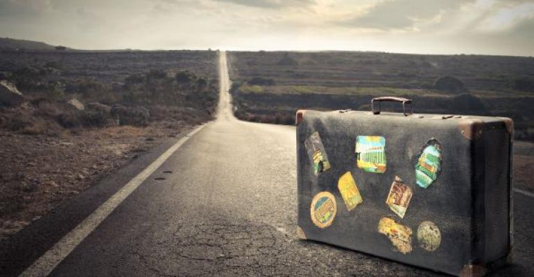 Old vintage suitcase in the middle of a road